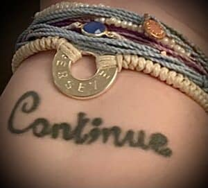 """The author's tattoo """"Cont;nue"""" with bracelets"""